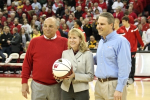 UW-Madison Athletic Director Barry Alvarez, Alliant Energy Senior Vice President John Larsen and Valerie Johnson, CEO of Habitat for Humanity of Dane County, appear at center court after Johnson was presented with a game ball before the January 20 Wisconsin-vs.-Iowa basketball game at the Kohl Center.